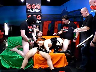 Kinky redhead in latex gangbanged by a big group of guys